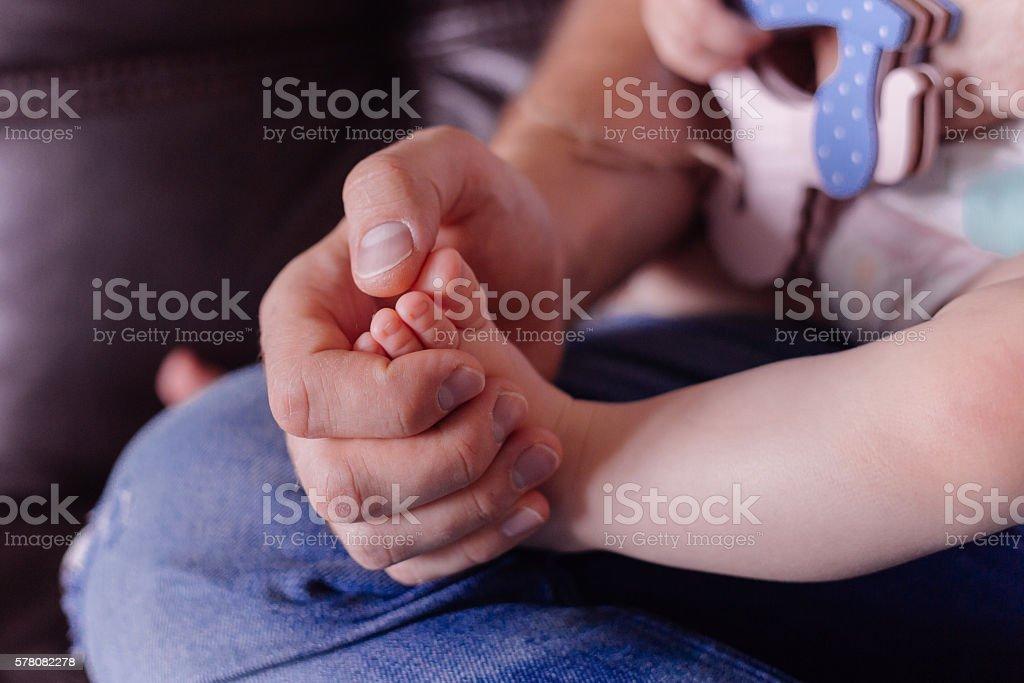 Man hold baby leg in hand stock photo