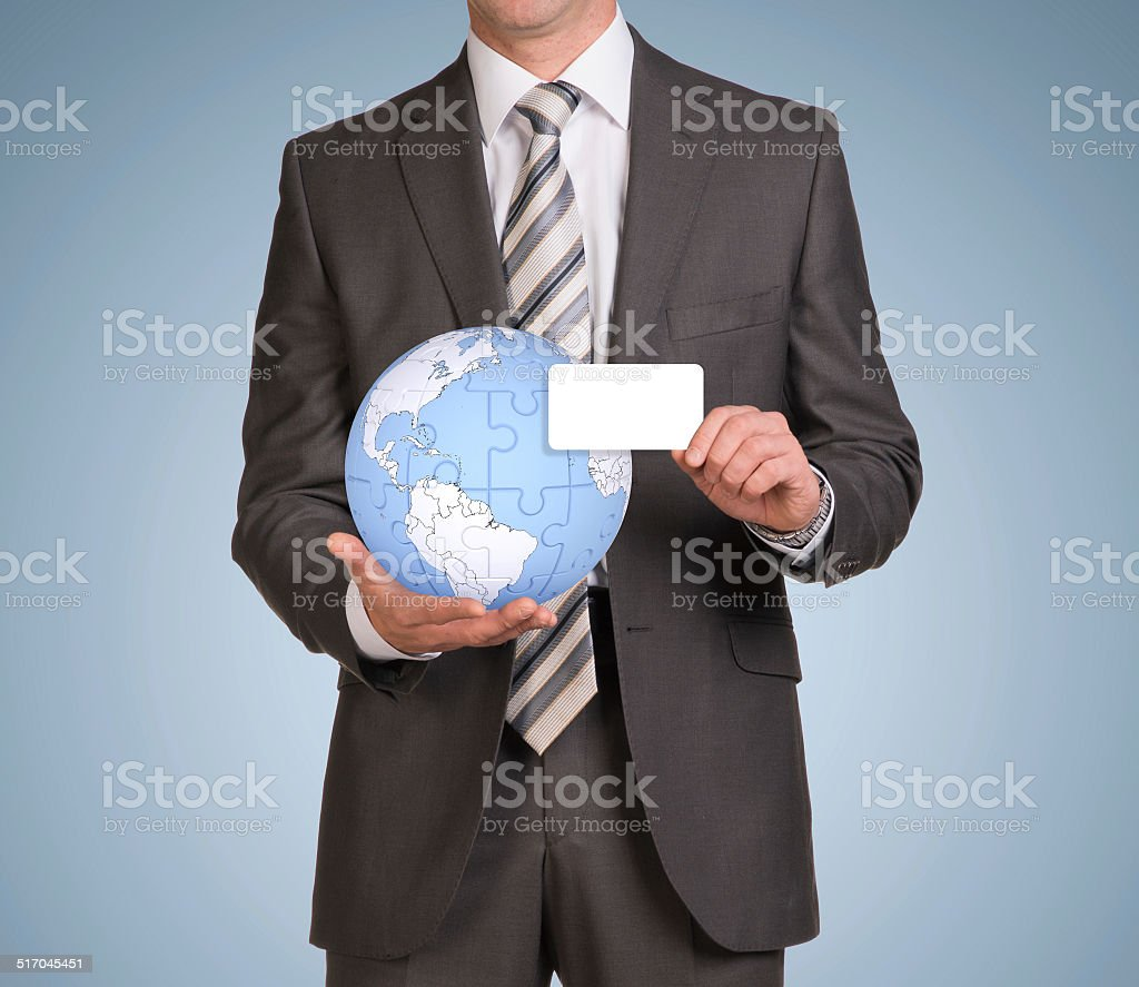 Man hold empty card and earth globe consisting of puzzles stock photo