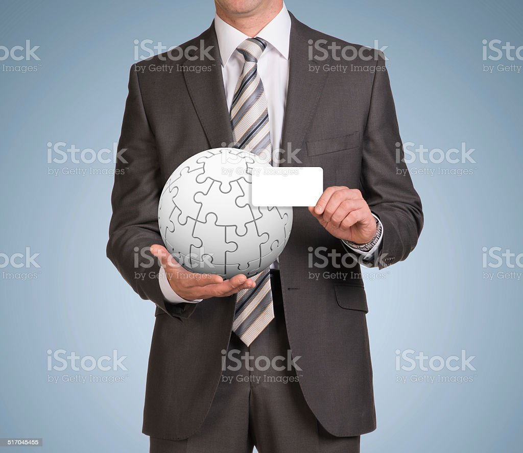 Man hold empty card and jigsaw puzzle sphere stock photo