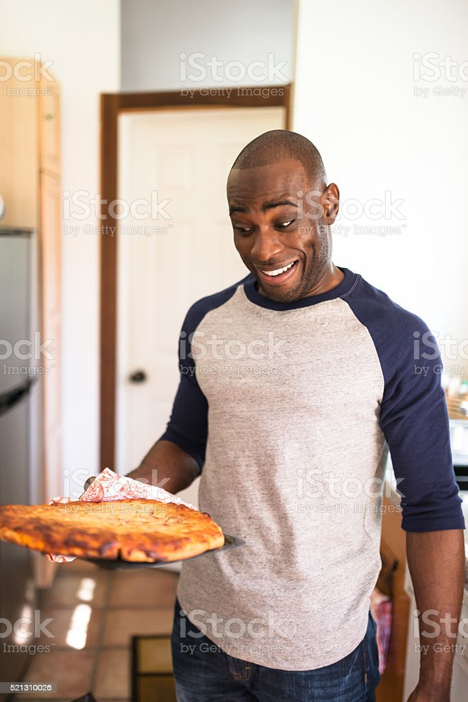 man holding a baked pizza stock photo