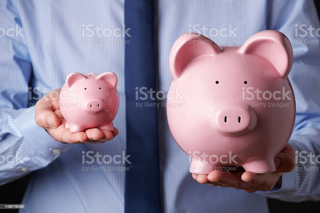 Man holding a big and small piggy bank on each hand royalty-free stock photo