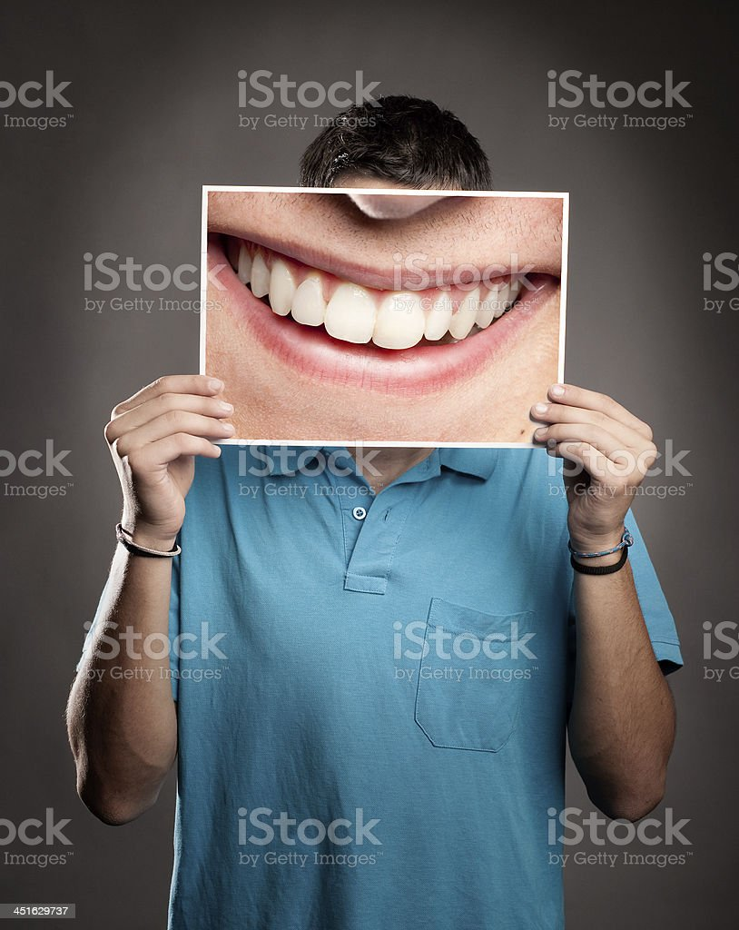 Man holding a big picture of a smile over his face stock photo