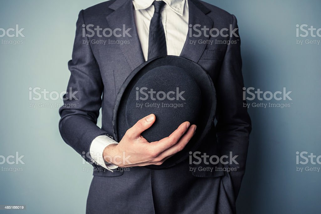 Man holding a bowler hat stock photo