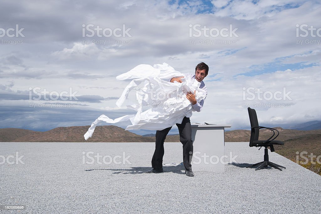 Man holding a bunch of papers in the wind royalty-free stock photo