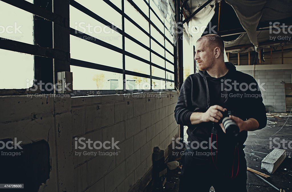 Man holding a camera looking through a window stock photo
