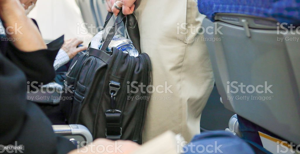 Man holding a carryon suitcase in the isle of airplane stock photo
