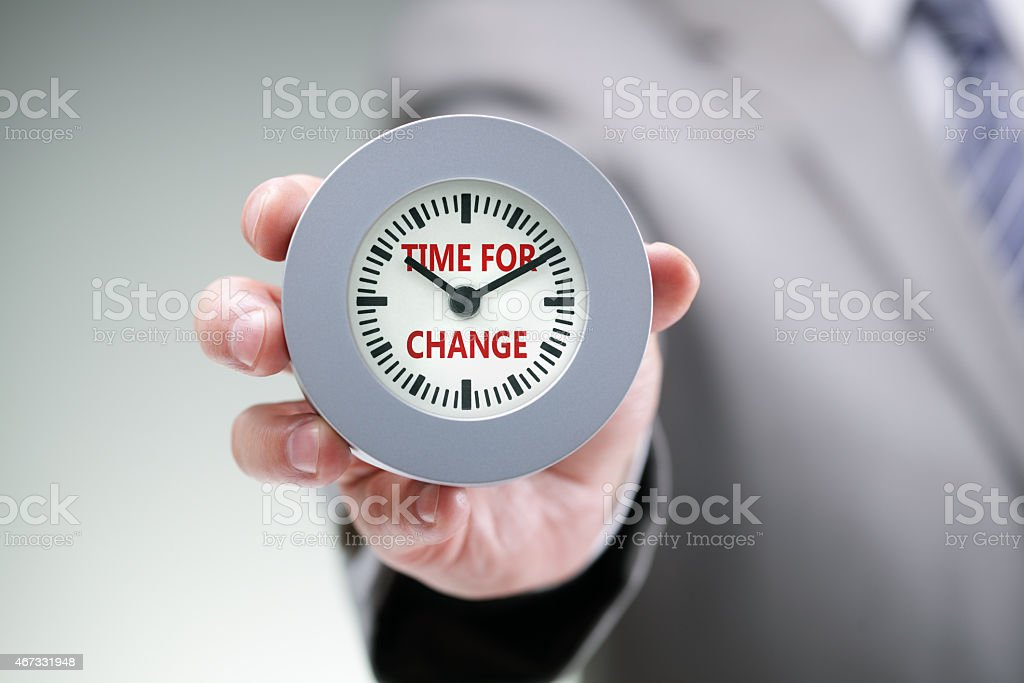 A man holding a clock that says time for change stock photo