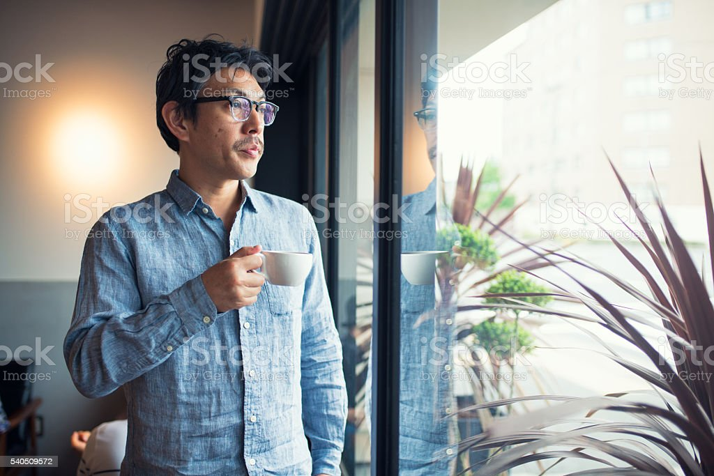 Man holding a coffee cup looking through window stock photo
