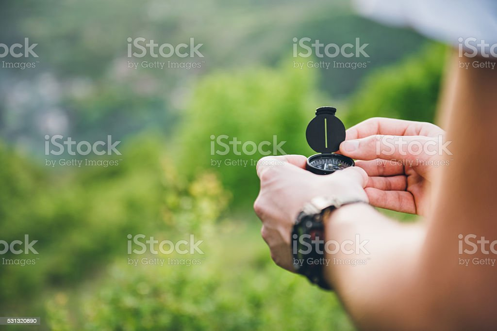 Man holding a compass stock photo