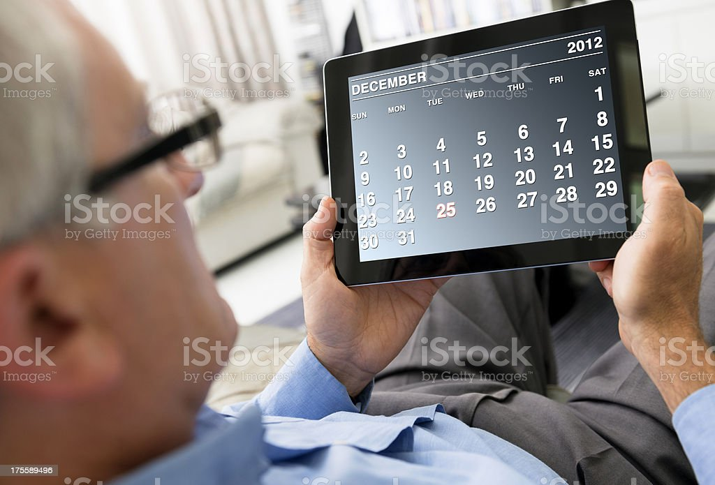 Man holding a digital tablet with December 2012 calendar royalty-free stock photo