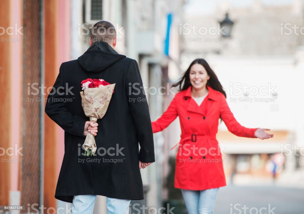 Man holding a flower bouquet behind his back, close up stock photo