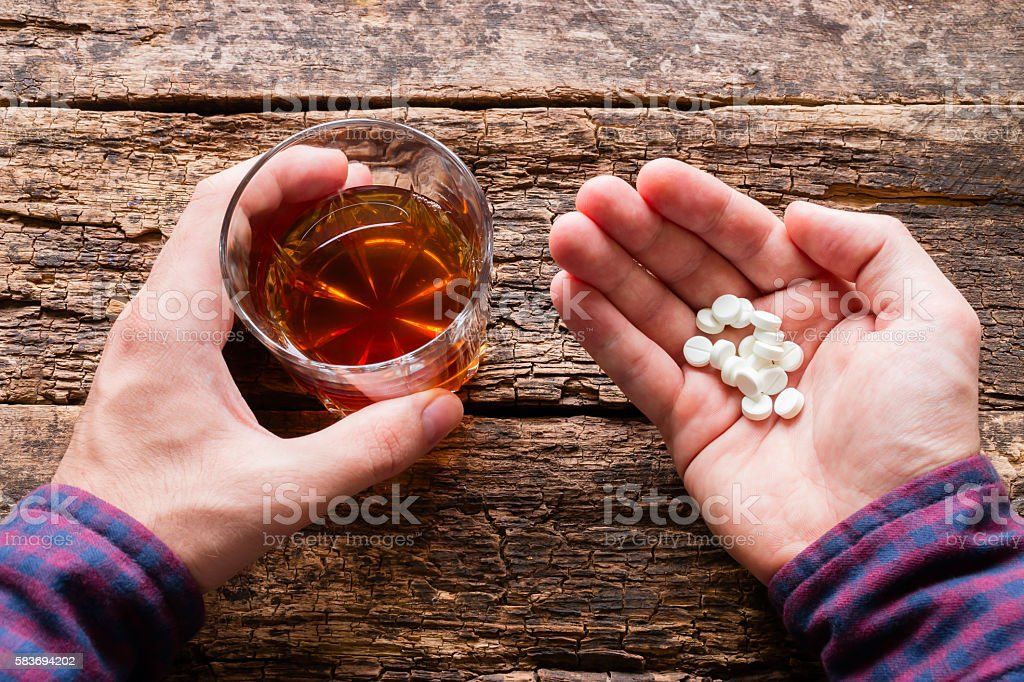 man holding a glass of alcohol and pills stock photo