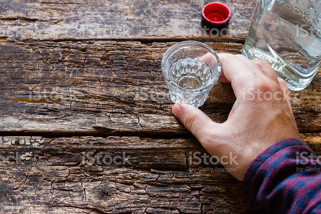 man holding a glass of vodka stock photo