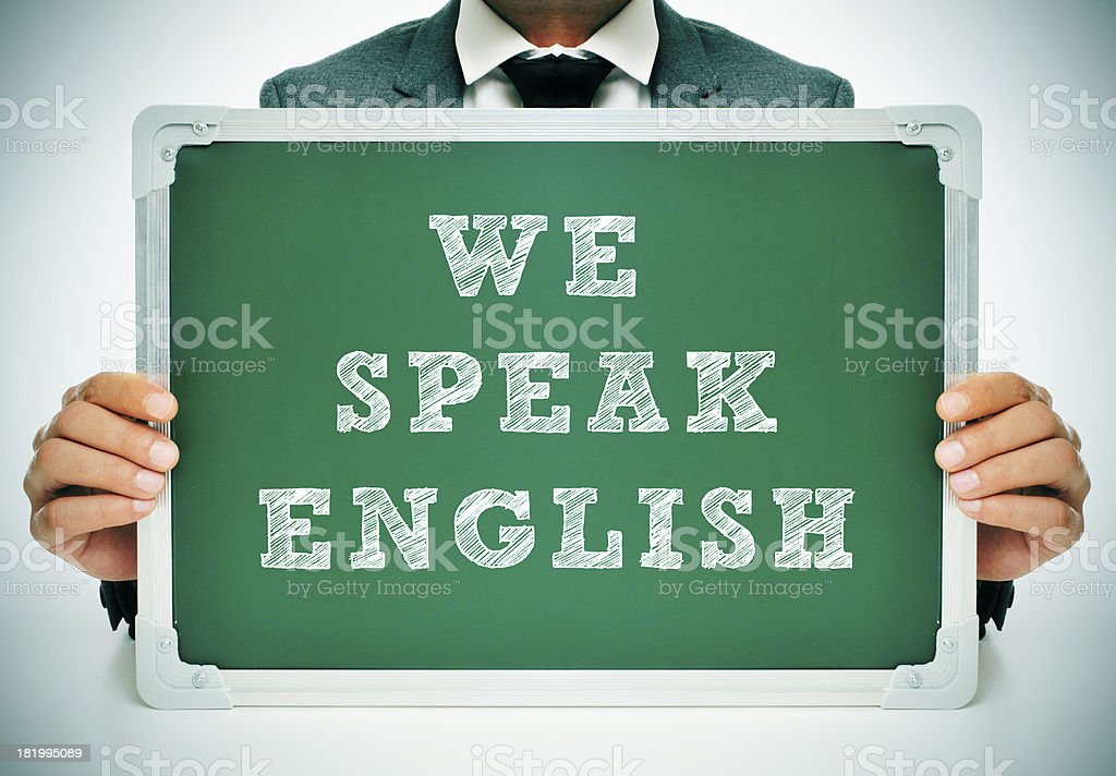 Man holding a green sign that says We speak English stock photo