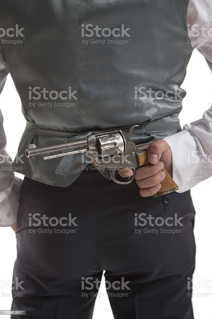 Man holding a gun behind his back stock photo