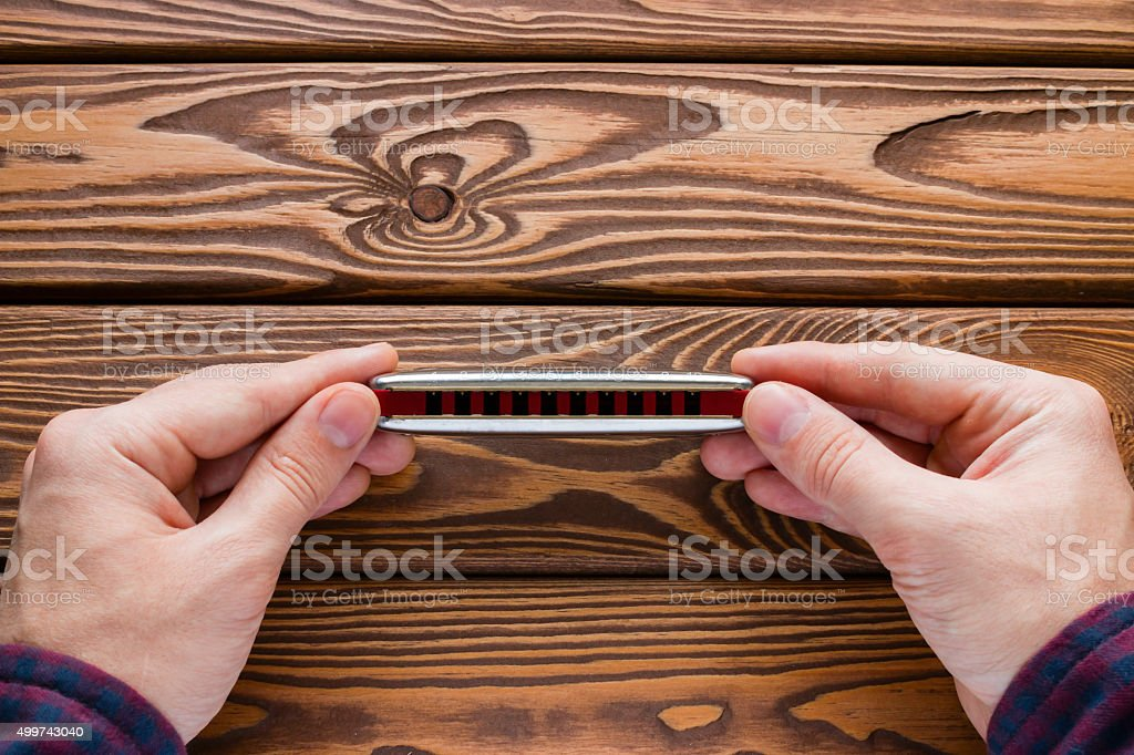 man holding a harmonica on a wooden background stock photo