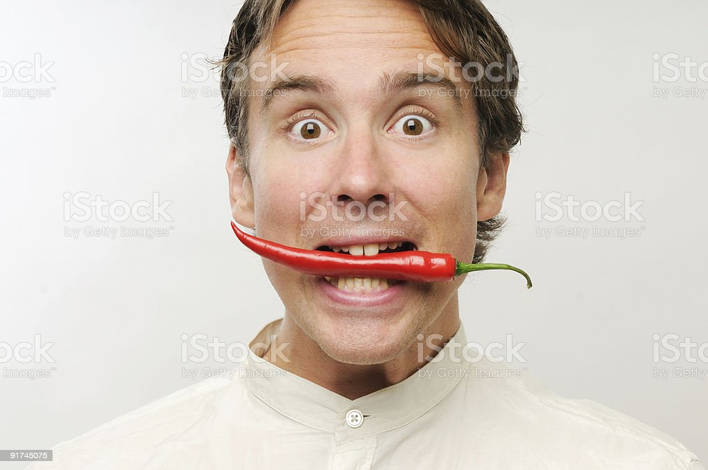 Man holding a long red chili in his mouth on white backing stock photo