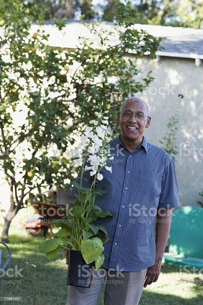 Man holding a potted plant outdoors stock photo