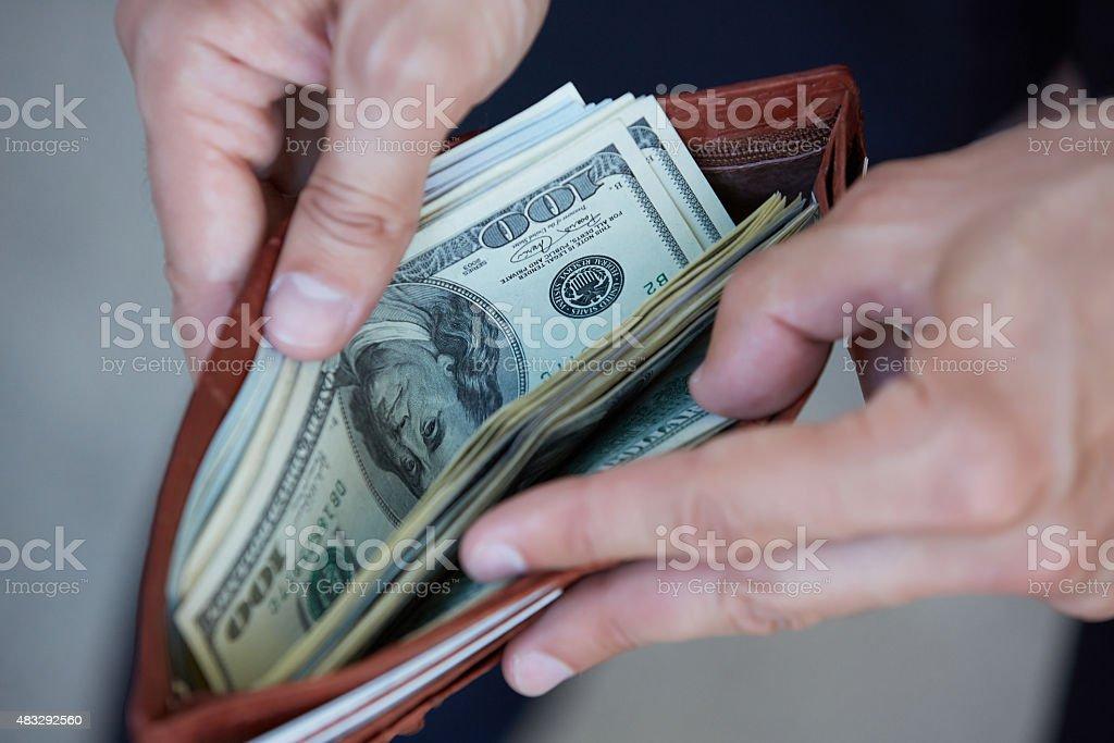 man holding a purse with money closeup stock photo