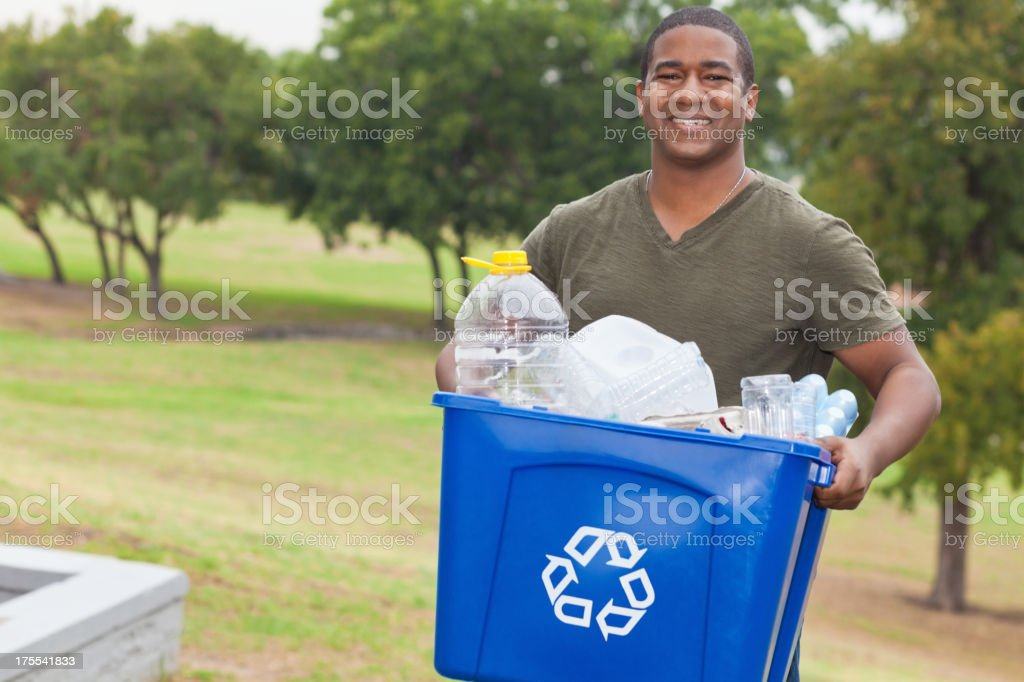 Man holding a recycle bin full of garbage royalty-free stock photo