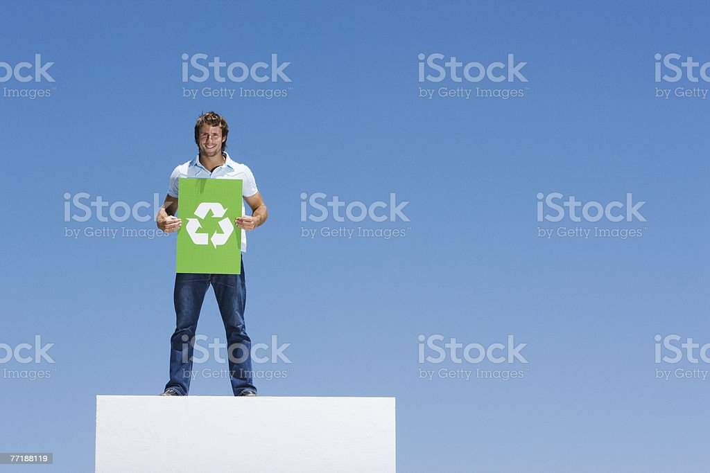 A man holding a recycling sign atop a wall royalty-free stock photo
