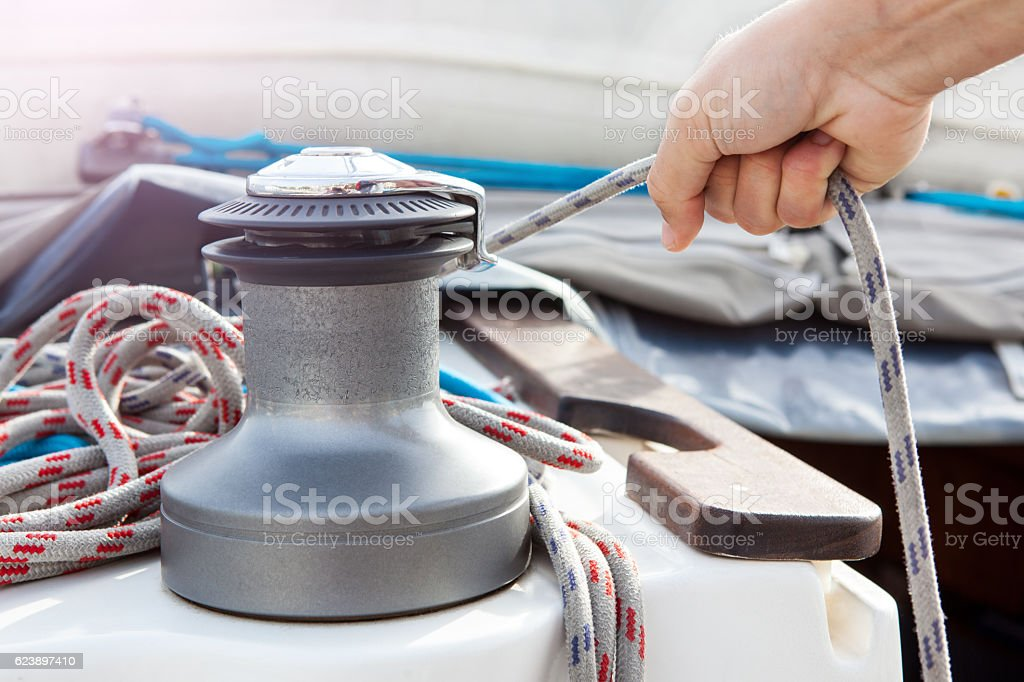 Man holding a rope in  boat stock photo