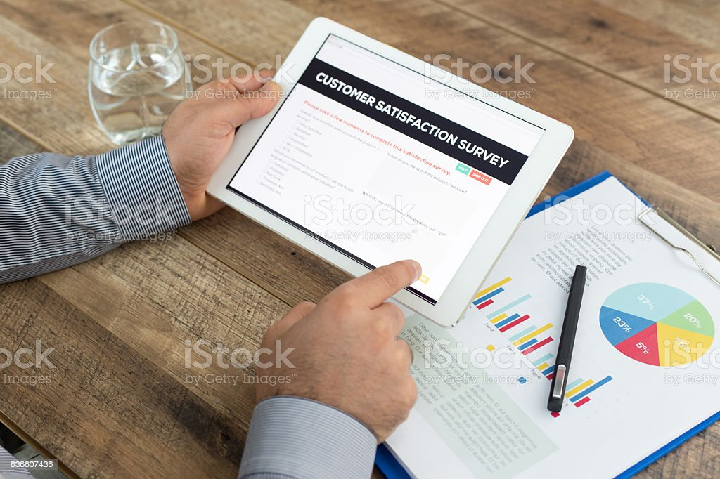 Man holding a tablet showing Customer Satisfaction Survey concept stock photo
