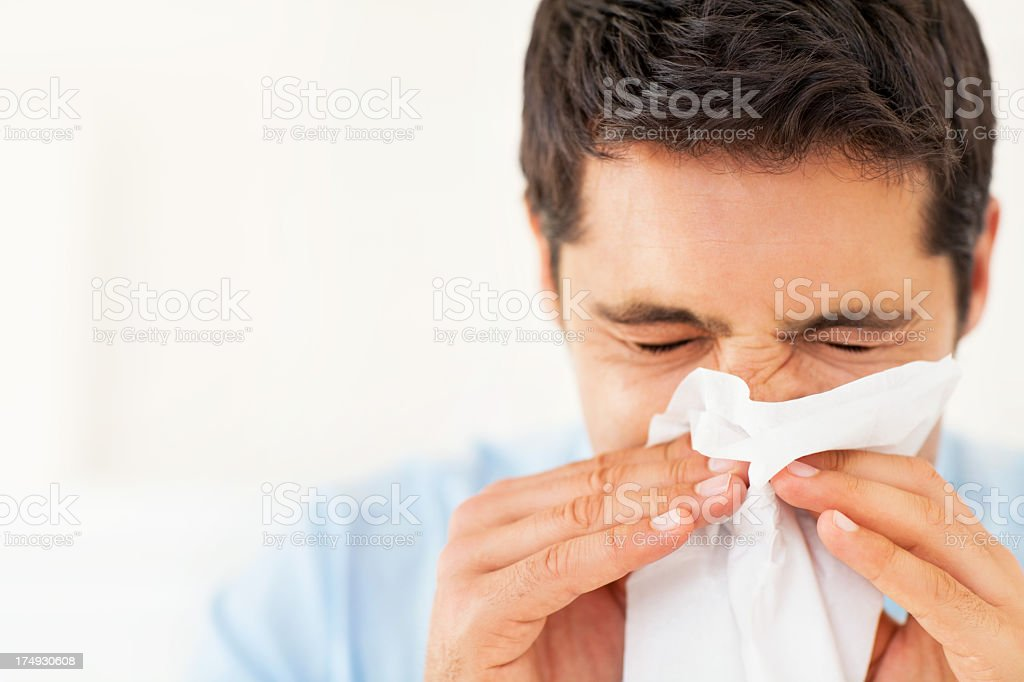 A man holding a tissue and blowing his nose stock photo