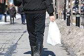 Man holding a white plastic bac in winter