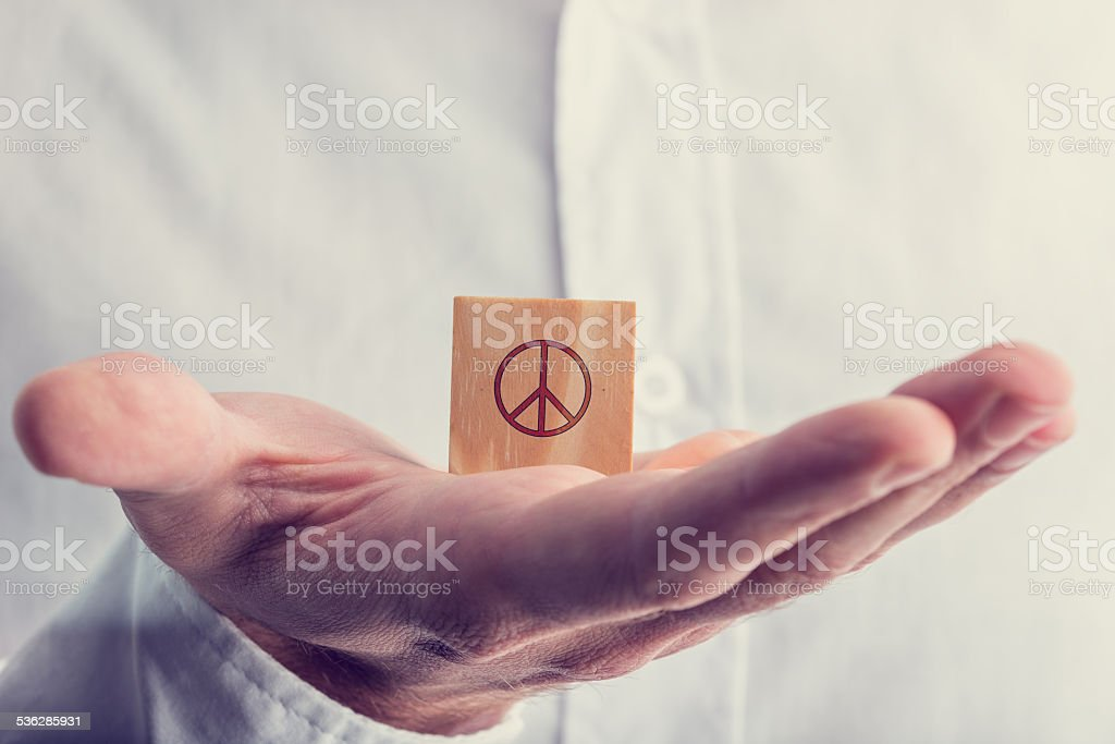 Man holding a wooden block with the peace sign stock photo