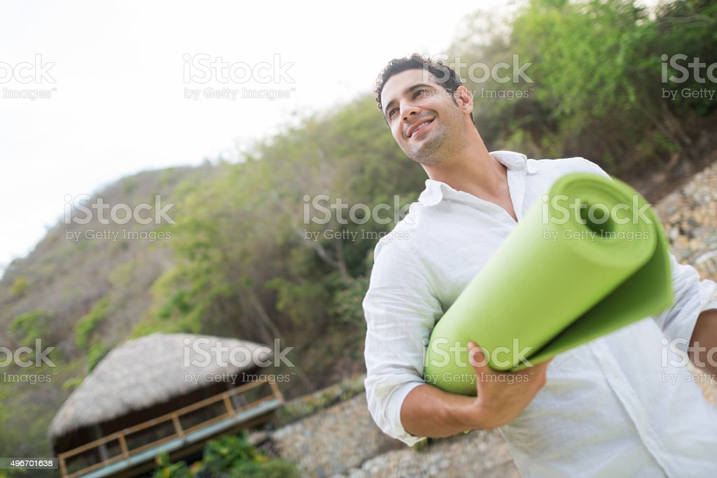 Man holding a yoga mat at a spa stock photo