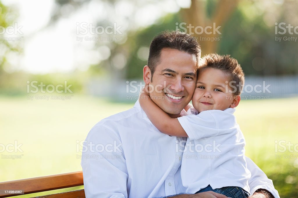 A man holding a young boy while sitting on a bench stock photo