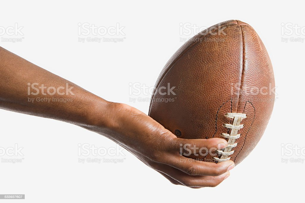 Man holding american football stock photo