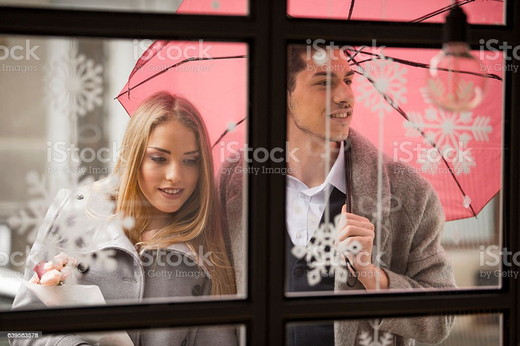 Man holding an umbrella for his girlfriend stock photo