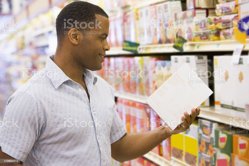 Man holding and looking at cereal box in shopping aisle stock photo