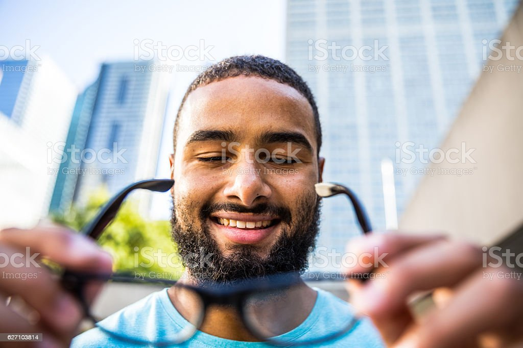 Man holding and putting his own glasses on stock photo