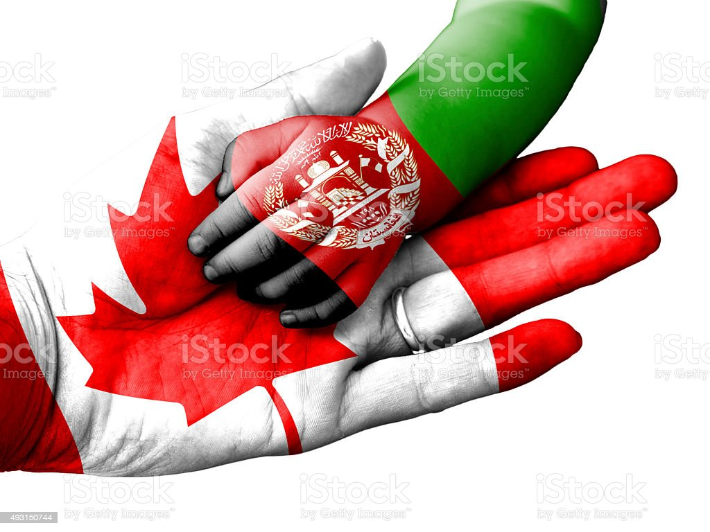 Man holding baby hand, Canada and Afghanistan flags overlaid stock photo