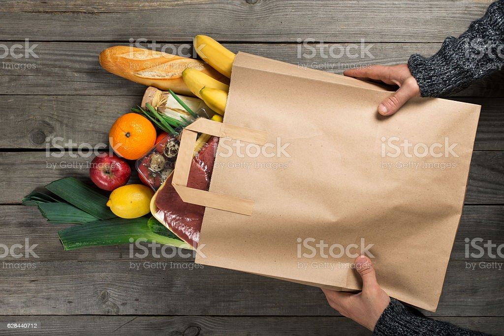 Man holding bag of different healthy food on wooden kitchen stock photo