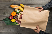 Man holding bag of different healthy food on wooden kitchen