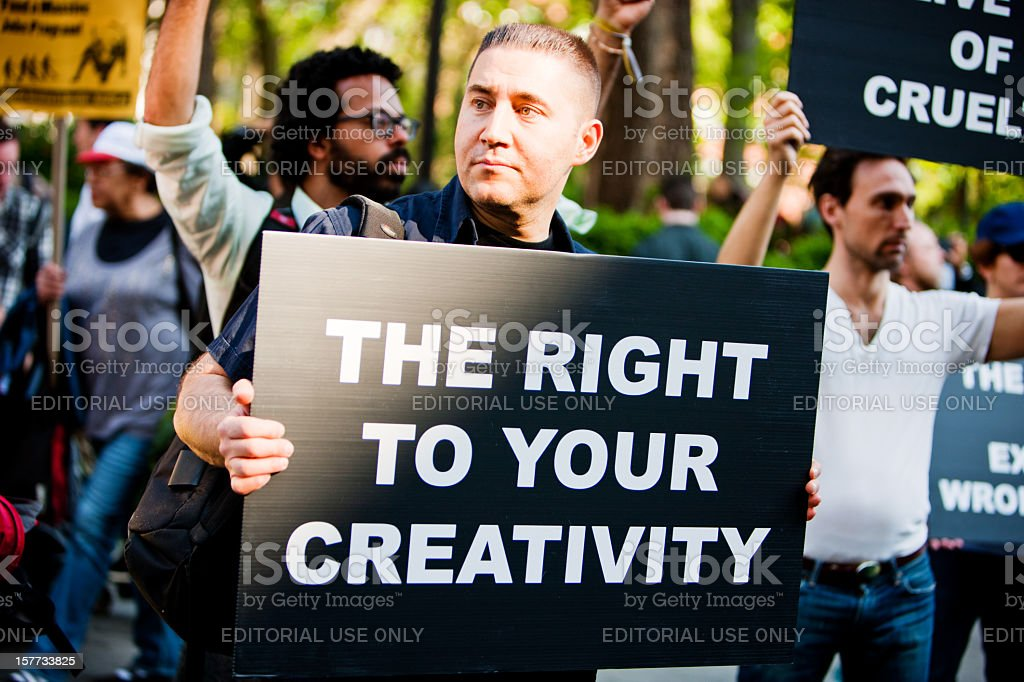 Man holding banner in crowd of protestors, New York stock photo