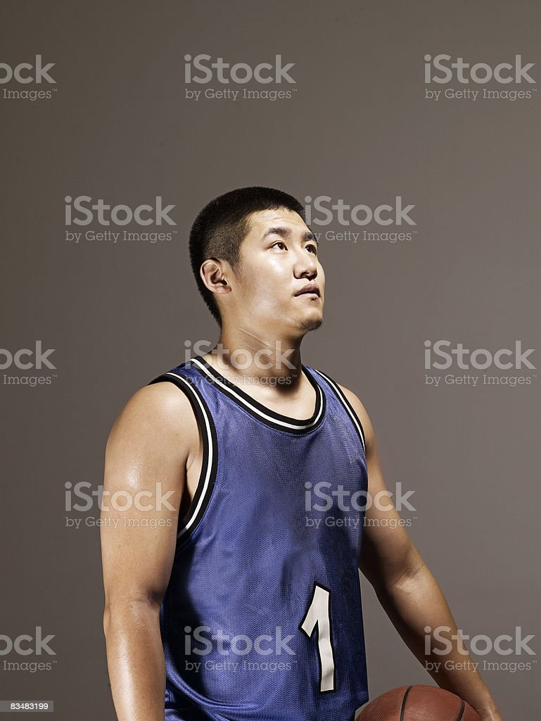 Man holding basketball, looking up stock photo
