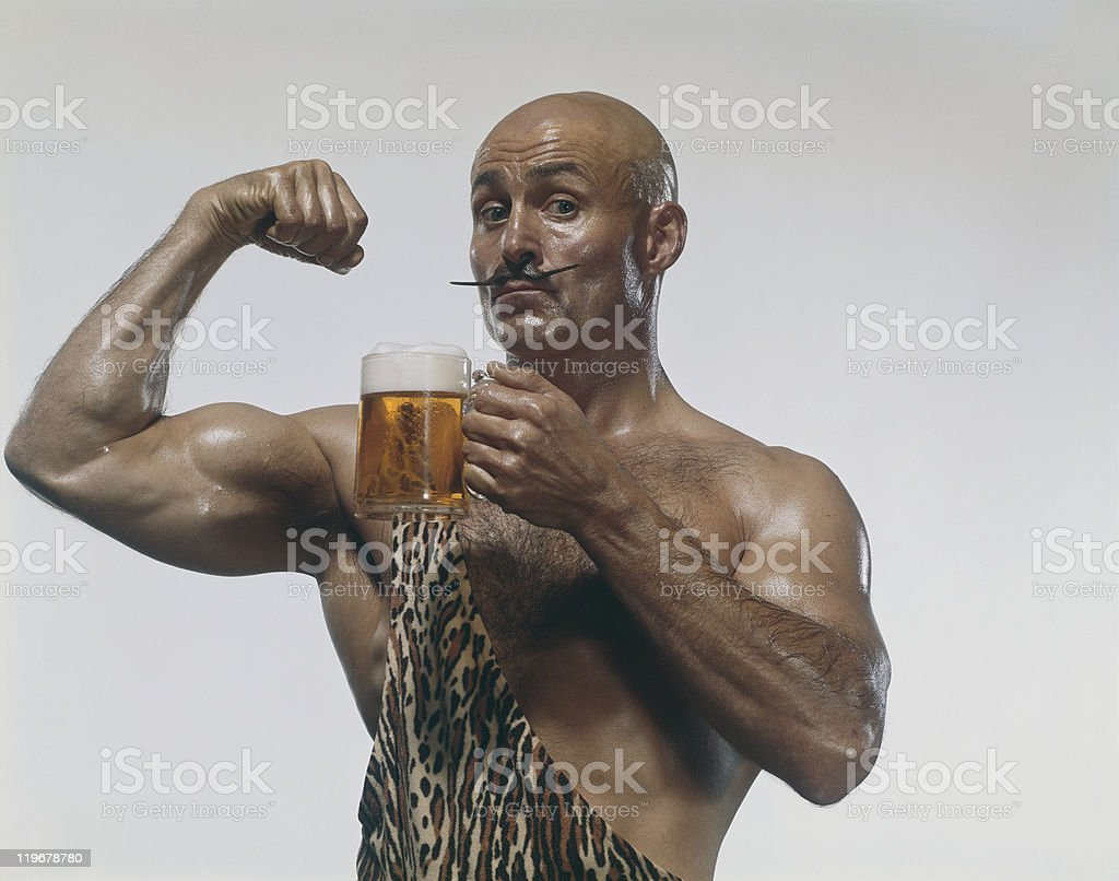 Man holding beer glass and showing muscle, close-up, portrait royalty-free stock photo