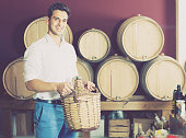 man holding big wicker bottle with wine