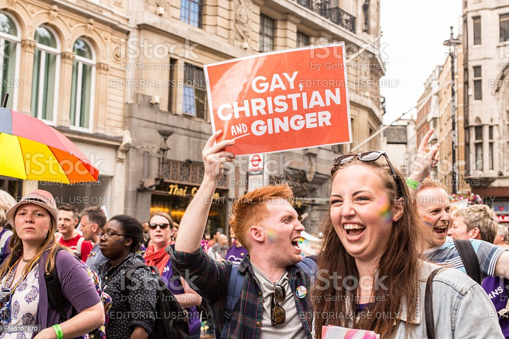 Man holding billboard gay, christian and ginger stock photo