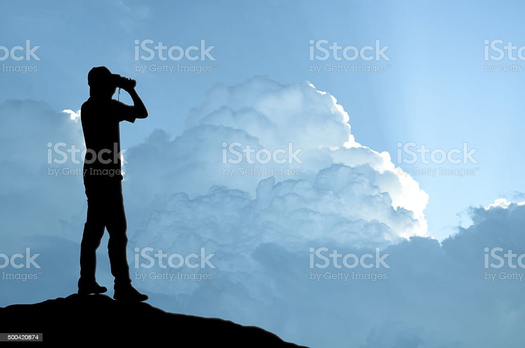 Man holding binocular on sunlight background stock photo