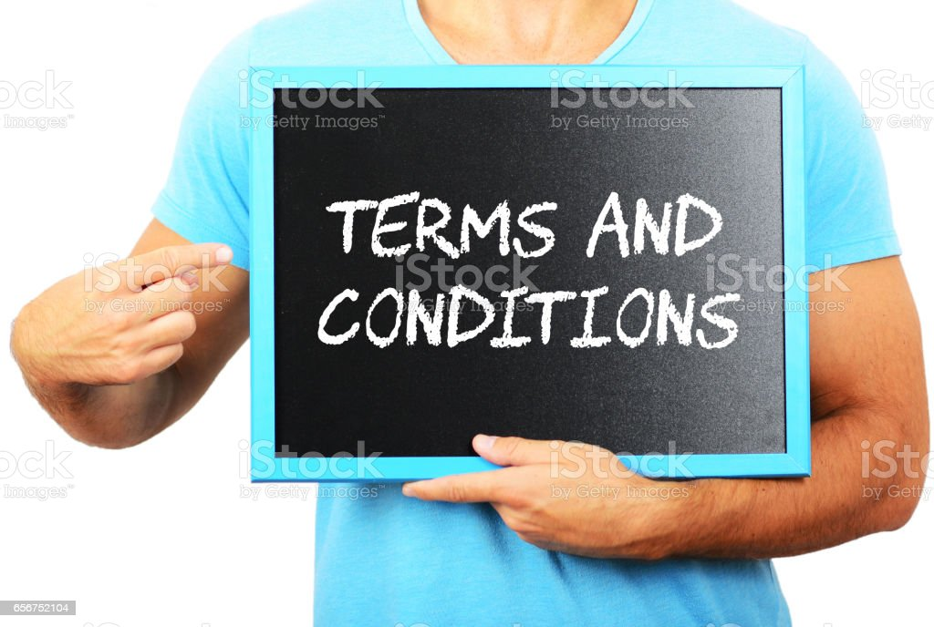 Man holding blackboard in hands and pointing the word TERMS AND CONDITIONS stock photo