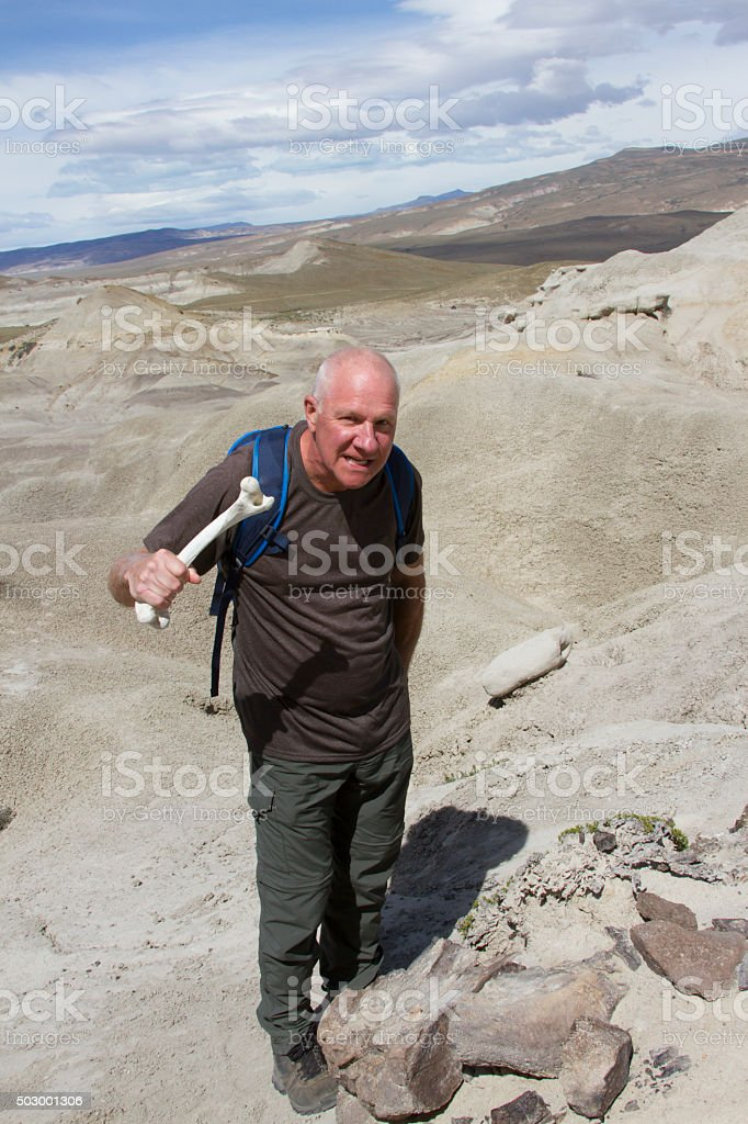 Man holding bone with dinosaur remains stock photo
