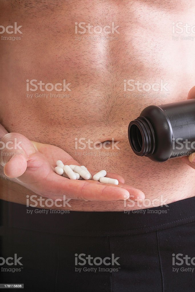 Man Holding Bottle and Pills royalty-free stock photo