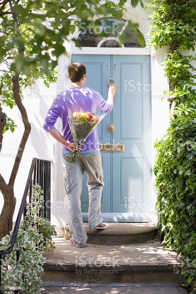 Man holding bouquet of flowers and knocking on door stock photo