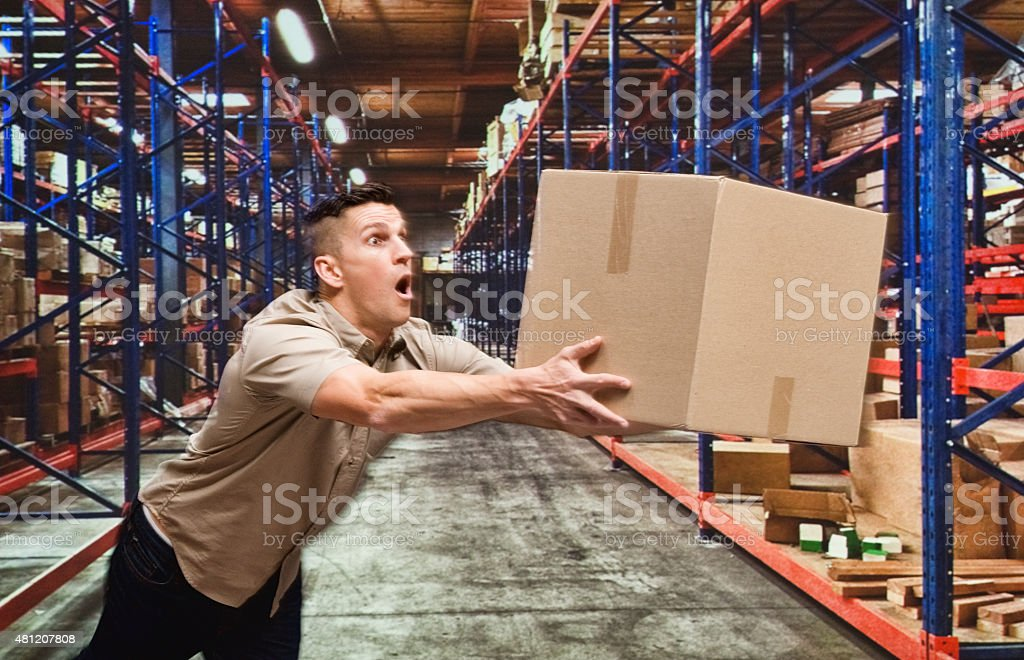 Man holding box and falling down stock photo